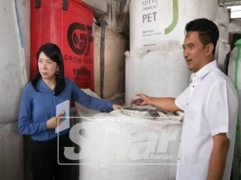 Bee Yin bersama Azmizam menunjukkan sisa plastik yang ditemui di kilang kitar semula plastik terpakai yang beroperasi secara haram di Teluk Gong semasa operasi penguatkuasaan bersepadu, petang tadi.