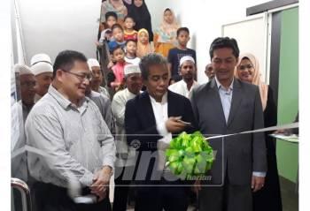Tengku Ahmad Badli Shah (tengah) memotong riben sebagai simbolik pelancaran Pejabat Jualan PMB Investment Negeri Kedah di Kompleks Sultan Abdul Hamid, dekat sini. Turut kelihatan, Najmi (tiga kanan).