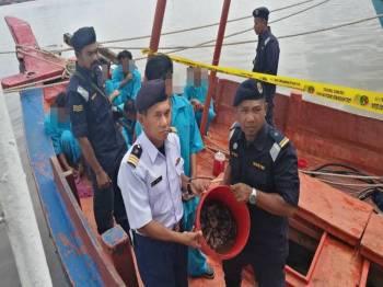 Ismail (kiri) menunjukkan gamat yang ditangkap nelayan Vietnam di perairan negara.