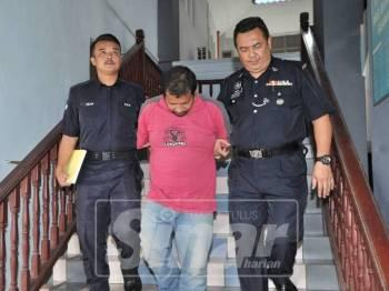 Tertuduh dibawa keluar dari mahkamah selepas dijatuhkan hukuman penjara dan sebatan selepas bersalah merompak beg tangan seorang wanita.