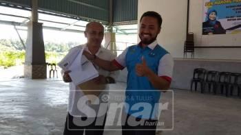 Farhash Wafa Salvador (kanan) menerima 252 borang keahlian baharu daripada seorang ahli PKR, Mohd Sutrizeno Suzari, 55, pada program tersebut.