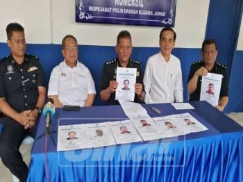 Mohd Abduh (tengah) menunjukkan senarai suspek yang dikehendaki polis.