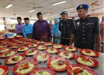 Azeem (kanan) dan Mohd Rashid (tebgah) memantau makanan yang terdapat di kantin itu ketika pemeriksaan kantin di Sekolah Kebangsaan (SK) Kampung Tun Abdul Razak di sini, hari ini.