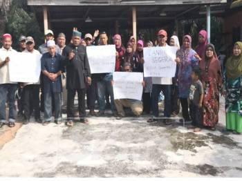 Penduduk memegang sepanduk mendesak kerajaan negeri mempercepat pelantikan pengerusi MPKK.
