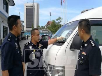 Suffian (tengah) menunjukkan van putih yang turut dirampas.