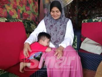 Rahimah melayan anak bongsunya, Mikail ketika ditemui tadi.