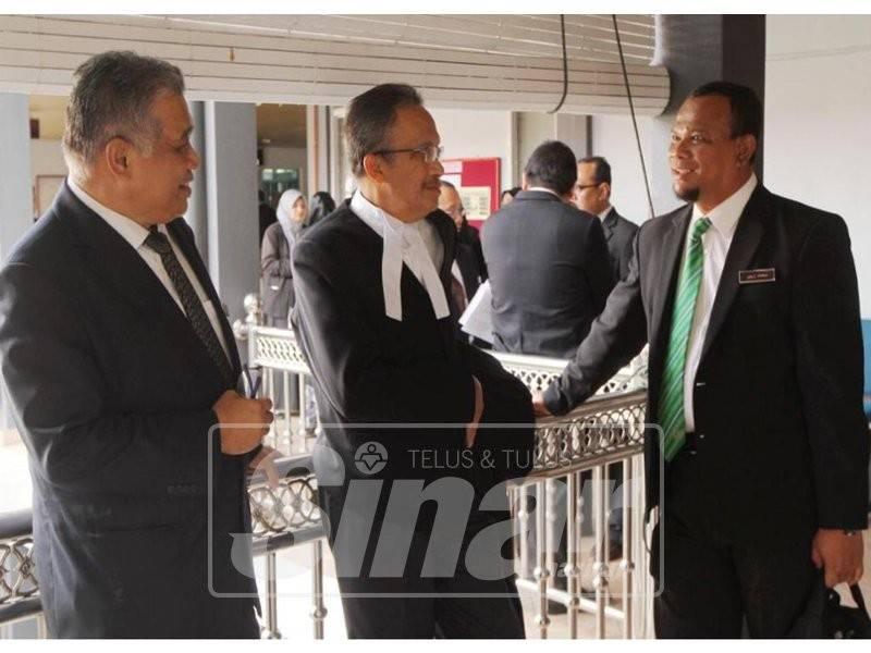 Shahidani (kiri) berbincang sesuatu dengan beberapa peguam yang mewakili Kelantan ketika mengadiri sebutan semula kes saman Kerajaan Persekutuan terhadap kerajaan Kelantan di Mahkamah Tinggi Kota Bharu hari ini.