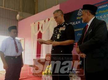 Hasanuddin (tengah) menyampaikan watikah pelantikan Pemimpin Kecil di SK Suria 1 di sini hari ini.