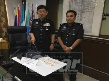 Chee Khoon (kiri) menunjukkan dadah dan barang dirampas pada sidang media di Bilik Mesyuarat IPD Sabak Bernam, di sini.