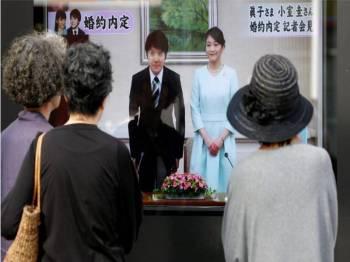 Orang ramai menonton paparan televisyen yang menyiarkan pengumuman pertunangan Komura dan Puteri Mako pada September 2017.