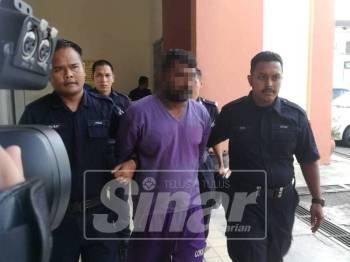 Tertuduh (tengah) dibawa anggota polis ke kamar perbicaraan di Mahkamah Majistret Taiping, petang tadi.