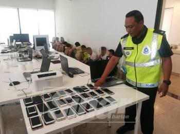 Mohd Khaizam menunjukkan barang yang dirampas.
