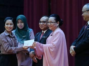 Pengarah Pendidikan Sabah, Mistirine Radin menyampaikan surat penempatan kepada seorang guru pada majlis Taklimat dan Penyampaian Surat Penempatan Guru Baharu Sekolah Rendah, hari ini. - Foto Bernama
