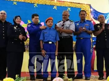 Roslan (tiga, kiri) dan Shafruddin (tiga, kanan) memakaikan tanda pangkat Lans Koperal kepada Syukur.