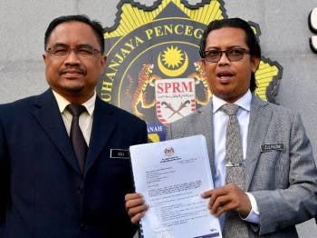 Zulhazmi (kanan) menunjukkan laporan yang dibuat berhubung pencerobohan dua lot tanah kerajaan di Medan Imbi, Bukit Bintang sebelum diserahkan kepada Suruhanjaya Pencegahan Rasuah Malaysia (SPRM) hari ini. - Foto Bernama