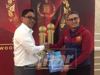 Khuzzan (kiri) bersalaman dengan Mohd Gadaffie pada sidang media berkenaan.
