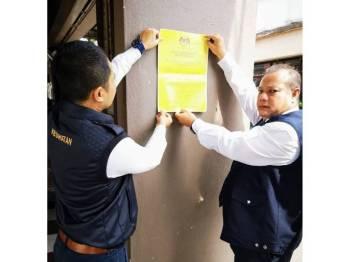Wan Mohd Suhaimi (kanan) menampal notis penutupan di sebuah kopitiam yang didapati kotor.