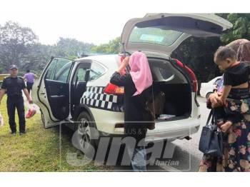 Anggota JPJ memunggah barang milik penumpang kereta ke kenderaan JPJ.