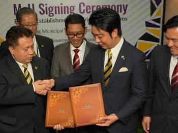 Ahmad Faizal (tengah) menyaksikan pertukaran dokumen MoU di antara Abd Rahim (kiri) dengan Soichiro di Bangunan Perak Darul Ridzuan. - FOTO PEJABAT MENTERI BESAR