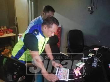 Mohd Khaizam melihat antara tablet yang disediakan premis bagi menawarkan permainan judi online.