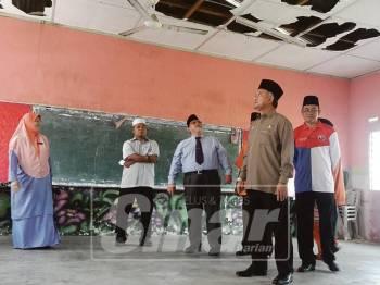 Aminolhuda (tiga, kiri) melihat keadaan bangunan SA Pengkalan Batu yang rosak akibat dimakan anai-anai.