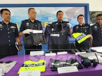 Shamsul Amar (tengah) menunjukkan seragam polis yang digunakan suspek dalam kegiatan penyamarannya.