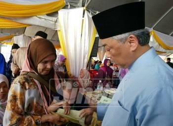 Al Sultan Abdullah (kanan) beramah mesra bersama penerima sumbangan, Rizal Rashid, 40 yang merupakan Orang Kurang Upaya (OKU) di Masjid Baharu Kuantan di sini, hari ini.