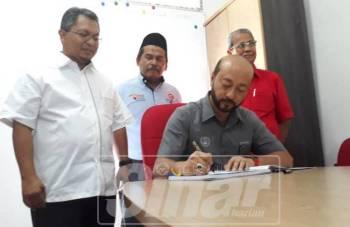 Mukhriz menandatangani buku pelawat selepas merasmikan Pusat Khidmat Rakyat Dun Sungai Limau, dekat sini. Turut kelihatan Zahran (kiri) dan Ku Abd Rahman (kanan).