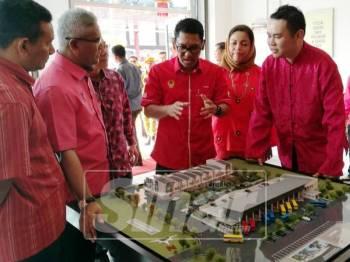 Ahmad Faizal berkata sesuatu ketika melihat model pembangunan kawasan pusat perdagangan Kampar, hari ini.