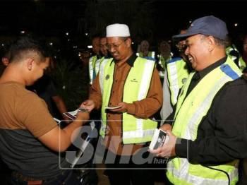 Mohd Nor (tengah) mengedarkan risalah kepada orang ramai sempena kempen pencegahan jenayah syariah di Pesisir Payang, semalam.