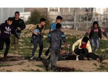 Rakyat Palestin mengangkat seorang rakan mereka yang cedera semasa menyertai protes di sempada Gaza, semalam.