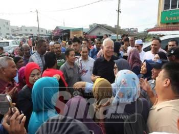 Kehadiran Najib di Pasar Tani Tapah disambut orang ramai yang mahu bersalaman dan mengambil gambar dengan beliau.