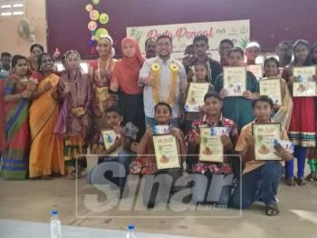 Mujahid (dua, kiri) menyerahkan sijil penghargaan kepada pelajar kaum India yang cemerlang dalam peperiksaan PT3 pada majlis sambutan Pesta Ponggal Parlimen Parit Buntar, hari ini.
