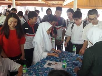 Cai Tung (kiri) melihat antara pelajar Jepun dan pelajar SMK Tun Syed Nasir Ismail bermain permainan tradisional.
