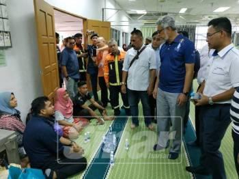 Khalid (tengah) melawat mangsa kebakaran diiringi Mohd Rani (kanan)