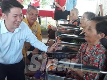 Simon (kiri) bertanya khabar seorang penghuni, Tai Kim Chi, 76 (kanan) selepas penyampaian sumbangan. Turut kelihatan Kee Tong (dua kiri).