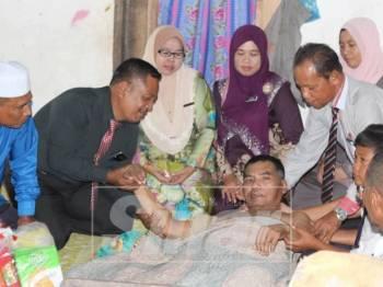Rokman memegang tangan Ramli yang terlantar di rumah di Kampung Bukit Mat Lipah.
