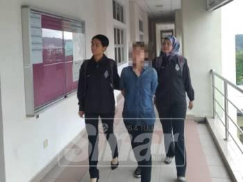 Lin San diiringi pegawai polis pada prosiding kes hari ini