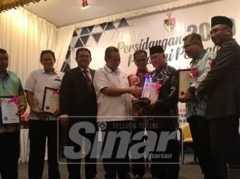 Aminuddin (empat, kiri) menyerahkan anugerah kepada Jabatan Mufti Negeri Sembilan yang memenangi pengurusan terbaik yang diterima Datuk Mohd Yusof Ahmad.