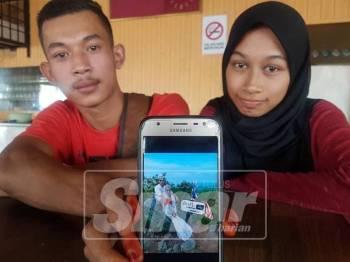 Mohd Zizi dan Nabila Akma menunjukkan foto mereka berbusana pengantin di atas Bukit Harimau Menangis, Kemasik yang tular di media sosial.