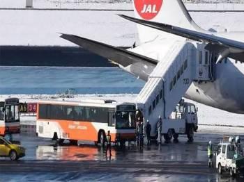 Penumpang dibawa keluar dari pesawat terbabit di Lapangan Terbang Narita.