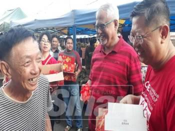 Dari kanan, Kok Yew dan Mahfuz ketika turun pada Program Serahan Buah Limau Sempena Tahun Baharu Cina di Market Cowboy, Jalan Teluk Wanjah, dekat sini, hari ini.