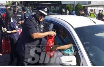 Kumaran menyampaikan kit pemanduan cermat di Plaza Tol Bukit Jelutong, Lebuhraya Guthrie, hari ini.
