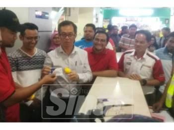 Chee Leong (empat, kanan) menyerahkan kit ujian saringan air kencing kepada seorang pemandu pada operasi itu yang dijalankan di Melaka Sentral, di sini, tadi.