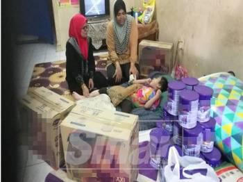Haslizah (tengah) menjaga Adawiyyah yang terlantar di rumah akibat pelbagai penyakit kronik selain ketumbuhan otak.
