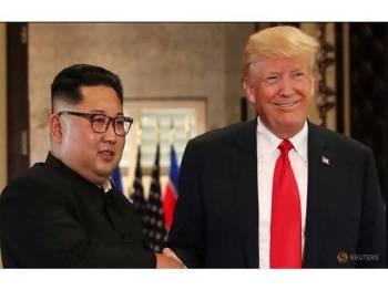 Jong-Un (kiri) dan Trump bersalaman ketika persidangan pertama di Singapura pada tahun lalu. - Foto Reuters