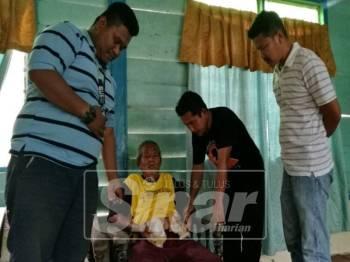 Mohd Yusoff menunjukkan beg khas di perutnya kepada Haniff (kanan) dan Rahman (dua, kiri) yang menziarahinya.