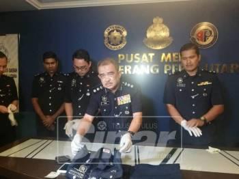 Noorzainy menunjukkan seragam polis yang digunakan suspek ketika melakukan jenayah.