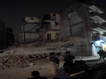 Beberapa lelaki berdiri di tepi bangunan yang runtuh di kawasan kediaman di bandar Luxor di selatan Mesir. Ia mengakibatkan seorang pelancong wanita dan dua kanak-kanak warga Mesir terbunuh.