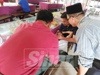 Abd Aziz (kanan) meriba dan mengurut anak muridnya perlahan-lahan sambil dibantu oleh guru-guru yang lain.